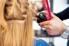 Blondine am Friseursalon unter Verwendung eines Berufswerkzeugs Stockfotos