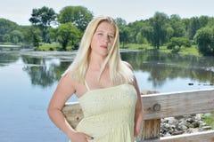 Blondine in gelben sundress Haltungen auf Brücke Lizenzfreie Stockfotografie