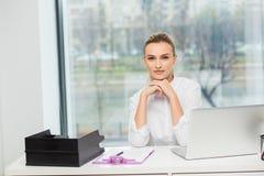 Blondine hinter ihrem Schreibtisch Stockfotos