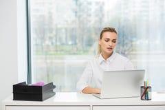 Blondine hinter ihrem Schreibtisch Stockbilder