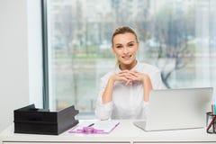 Blondine hinter ihrem Schreibtisch Lizenzfreie Stockfotografie