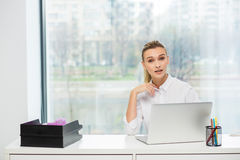 Blondine hinter ihrem Schreibtisch Lizenzfreies Stockbild