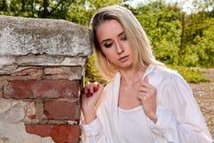Blondine im alten sonnigen Sommerstadtpark r lizenzfreie stockfotografie