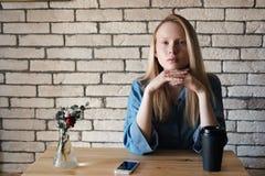 Blondine im blauen Hemd sitzt am Tisch in einem Café, auf dem eine schwarze Papierschale mit Kaffee steht und die Kamera betracht Stockfoto