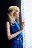 Blondine im blauen Kleid, das am Fenster steht, Frau fällt Schatten der Vorhänge Schönes sinnliches Porträt eines mysteriösen Mäd Lizenzfreies Stockbild