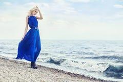 Blondine im blauen Kleid geht entlang die Promenade durch Meer, Sommerferien in Meer Schönes sinnliches Porträt eines mysteriösen Stockfotos