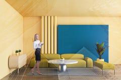 Blondine im gelben Wohnzimmer lizenzfreie stockfotografie