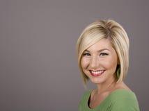 Blondine im grünen Blendung-Lächeln Lizenzfreies Stockfoto