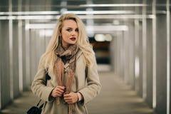 Blondine im Mantel an der Unterführung stockfotos