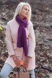 Blondine im Mantel mit Tasche Stockbilder