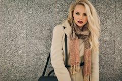 Blondine im Mantel nahe grauer Wand stockfoto