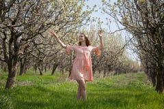 Blondine im rosa Kleid gehen durch einen blühenden Garten im Frühjahr Lizenzfreies Stockbild