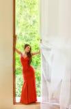 Blondine im roten Kleid nahe einem Fenster Lizenzfreies Stockfoto
