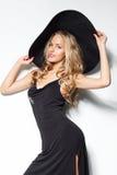 Blondine im schwarzen Hut und im Kleid werfen auf weißem Studio backround auf Stockbilder