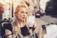 Blondine im Straßencafé mit Tasse Tee Lizenzfreies Stockfoto