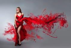 Blondine im windigen roten und weißen Kleid Stockfotos
