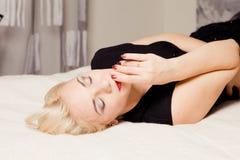 Blondine liegt auf Bett auf schwarzem Kleid Lizenzfreie Stockfotos