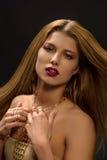 """Blondine mit angeredetem make†""""oben, langer Halskette und vielen Ringen auf ihren Fingern Lizenzfreie Stockbilder"""