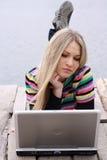 Blondine mit Computer nahe See Stockbilder