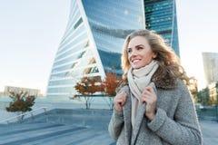 Blondine mit dem gelockten Haar und blaue Augen nähern sich Gebäude Stockfotografie