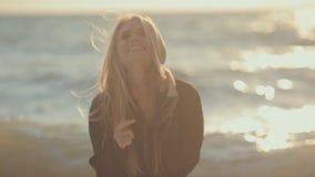 Blondine mit dem langen Haar, das in das Meer springt und stock footage