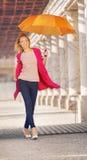 Blondine mit dem orange Regenschirm Lizenzfreie Stockfotografie