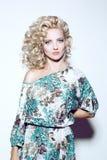 Blondine mit dem Volumenhaar in einem Kleid Lizenzfreie Stockfotos