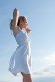 Blondine mit den Armen hob auf Hintergrund von Meer an Lizenzfreies Stockbild