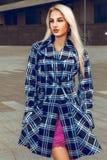 Blondine mit den blauen Augen, die draußen im Mantel aufwerfen Lizenzfreies Stockfoto