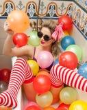 Blondine mit der Sonnenbrille, die in ihrem Badrohr mit hellen farbigen Ballonen spielt Sinnliches Mädchen mit weißen roten gestr Lizenzfreies Stockbild