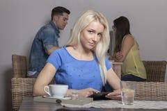 Blondine mit der Tablette, die in der Cafeteria sitzt Lizenzfreies Stockbild