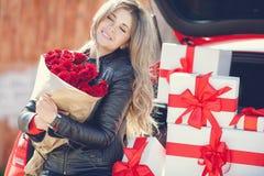 Blondine mit einem Blumenstrauß von Blumen und von Geschenken Stockbild