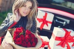 Blondine mit einem Blumenstrauß von Blumen und von Geschenken Stockbilder