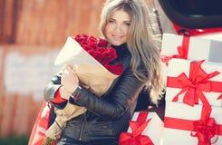 Blondine mit einem Blumenstrauß von Blumen und von Geschenken Lizenzfreies Stockbild