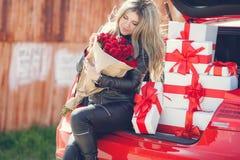 Blondine mit einem Blumenstrauß von Blumen und von Geschenken Stockfotografie