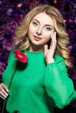 Blondine mit einem leichten Make-up, das die Kamera beim Halten der Blume nahe dem Gesicht auf einem Blumenhintergrund betrachtet Stockfotos