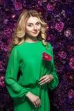Blondine mit einem leichten Make-up, das die Kamera beim Halten der Blume nahe dem Gesicht auf einem Blumenhintergrund betrachtet Lizenzfreies Stockbild