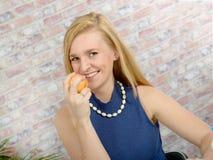 Blondine mit einer blauen Strickjacke mit Apfel Stockfotografie