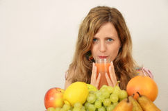 Blondine mit frischen Früchten und Orangensaft Lizenzfreie Stockfotografie