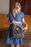 Blondine mit Gray Leather Purse Stockfoto