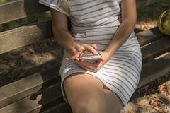 Blondine mit intelligentem Telefon im Park Lizenzfreie Stockfotografie