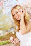 Blondine mit Kirschblüten in ihrem Haar Lizenzfreie Stockfotos
