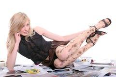 Blondine mit Mobile auf Zeitschriften Stockbilder