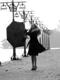 Blondine mit Regenschirm auf Promenade Stockfotografie