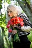 Blondine mit roten Tulpen Lizenzfreie Stockfotos
