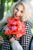 Blondine mit roten Tulpen Stockfoto