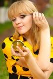 Blondine mit Spiegel und Tinte für Wimpern Stockbild