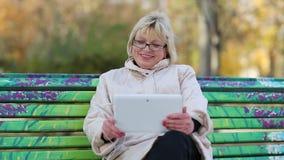 Blondine mit Tablet-PC sitzen auf der Bank und sprechen auf Skype stock video footage