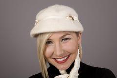 Blondine in Pelz-Hut-lachender Hand auf Kinn Stockfoto