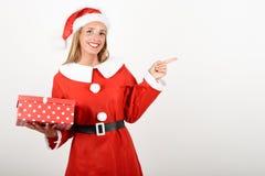 Blondine in Santa Claus-Kleidung lächelnd mit Geschenkbox Stockbilder